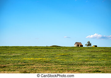 Old lonely house in the field on sunny day
