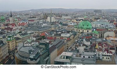 Old low-rise and modern buildings' roofs in Vienna on a cloudy day, Austria. 4K overview pan shot