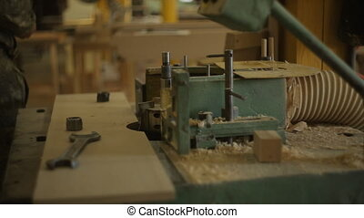 old machine for drilling round hole in the wooden plank in...