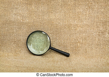 Old magnifier on brown canvas background