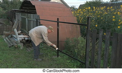 Old man 70s paints the iron fence using a black paint...