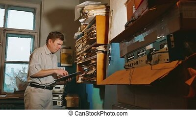 old man accountant in an old office examines paper reporting...