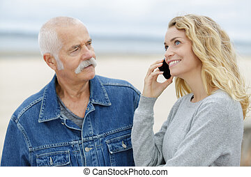 old man and beautiful daughter using a smartphone