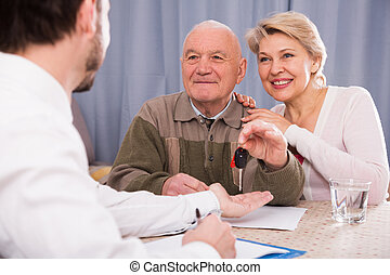 Old man and mature woman signing contract car lease and hand...