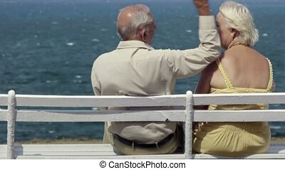 old man and woman on bench at sea