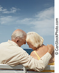 old man and woman on bench at the sea - senior caucasian...