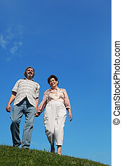 old man and woman standing on hill and holding for hands, blue sky and green lawn