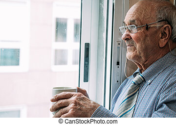 old man at home with cup of coffee at the window