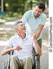 Old man at hospital - Adult son walking with disabled father...