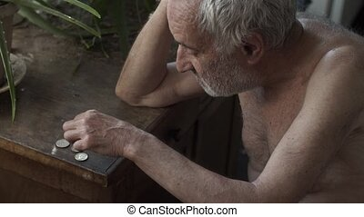 Old man counting coins on a table