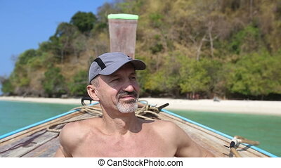 old man drifts in longtail boat to island beach