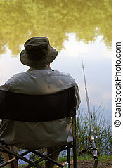 Old man enjoys fishing - An old man enjoys a perfect day of...