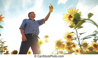 old man farmer holding in hand a plastic bottle sunflower...