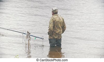 Old man fishing on the river, watching the fish and takes...