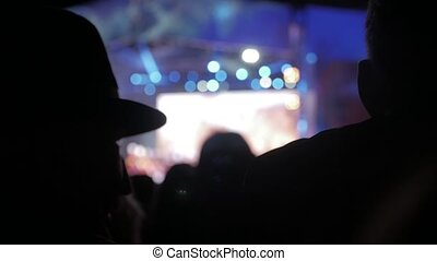 old man in a hat at . crowd at concert - summer music festival. Concert crowd attending a concert, people silhouettes are visible, backlit by stage lights. audience watching lifestyle the concert on stage concept