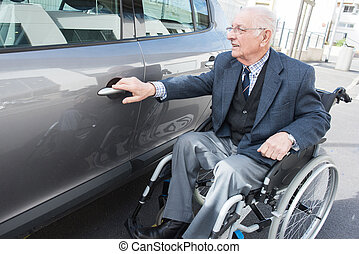 old man in a wheelchair next to his car