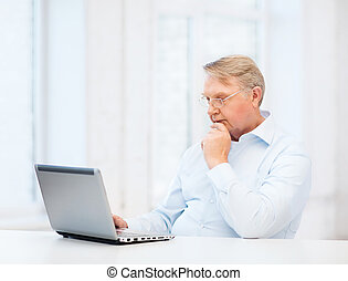 old man in eyeglasses working with laptop at home