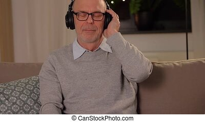 old man in headphones listening to music at home - ...