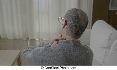 Old man in pain massaging his back neck having a muscle...
