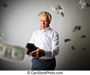 Old man in white and empty wallet. Falling dollars and taxes.
