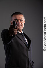 old man is a killer pointing a revolver