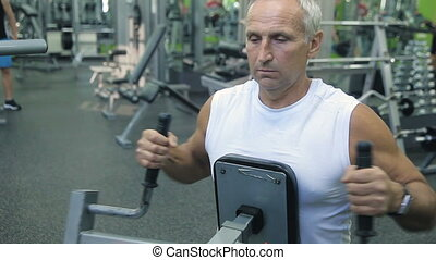 Old man is engaged on simulators in gym