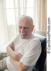 old man is sitting in a chair. Smiling old man sitting in a chair by the window, portrait, close-up