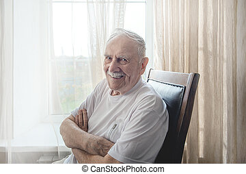 old man is sitting in a chair. Smiling old man sitting in a chair by the window, portrait, close-up, copy of space