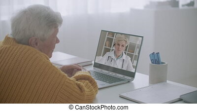 old man is talking with his family doctor by web camera, consulting and advising, listening her, viewing at display of notebook, staying home