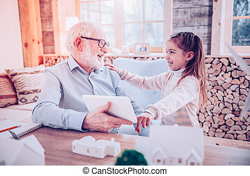 Old man laughing with his cute granddaughter