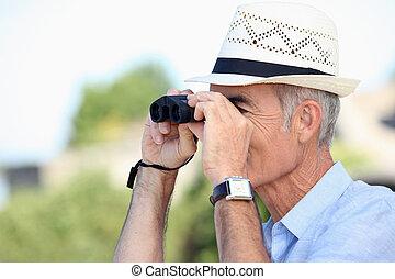 Old man looking through binoculars