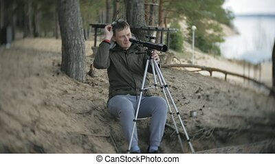 Old man looks through a telescope in a forest on the river...