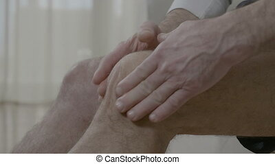Old man massaging his arthritic knee having joint ache at...