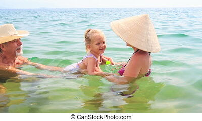 Old Man Mother Lift up Little Daughter Play in Azure Sea