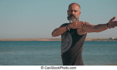 Old man of athletic build does exercises and yoga standing on sandy beach