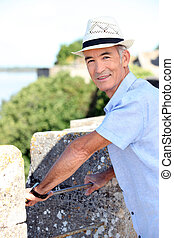 Old man on holiday leaning against wall