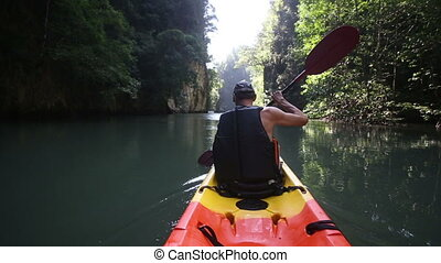 old man paddles on kayak down to river exit and looks around