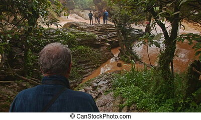 Old Man Picks Way along Path in Tropical Forest