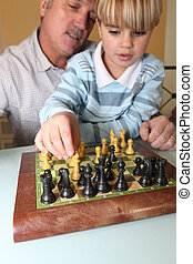 Old man playing chess with his grandson