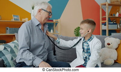Old man loving grandfather is playing with cute child examining him with stethoscope in house having fun pretending to be doctor and wearing white gown.