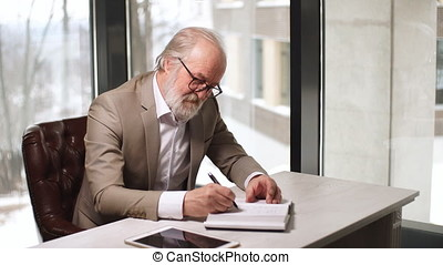 Old man pleasant man is writing his ideas in the notebook...