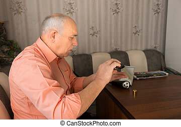 Old Man Pouring Aftershave Bottle on Hand - Close up Sitting...