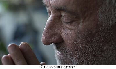Old man with wrinkles praying