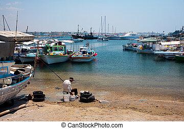 Old man preparing to fish off Paphos beach