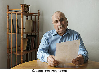 Old man reading a paper document or letter