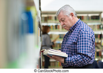 old man reading and choosing book in library