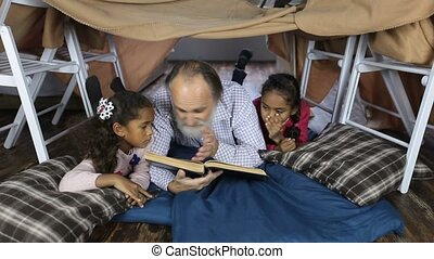 Old man reading the Bible with grandchildren - Affectionate...