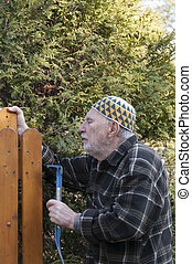 old man repairing a gate