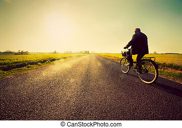 Old man riding a bike to sunny sunset sky