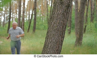 Old man running in the park then resting near tree stem and looking on a camera